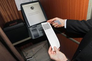 A man holds a voting receipt after an electronic voting system