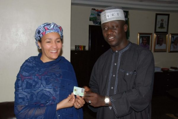 NIMC file photo shows Amina Mohammed, Minister of Environment of Nigeria (left) holding Nigeria National ID card, with Abdulhamid Umar, Head of Operations at NIMC, when the Minister enrolled for Nigeria National ID in Abuja