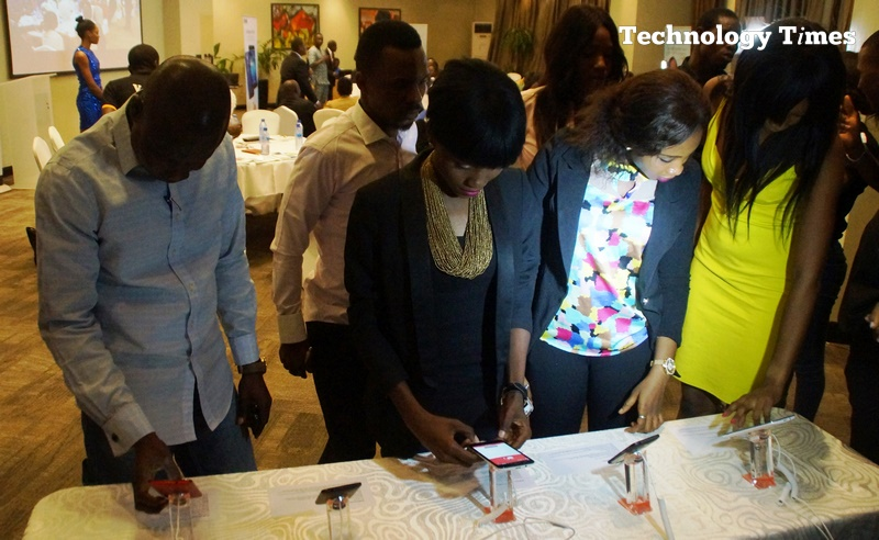 Technology Times photo shows people looking at smartphones on display at a mobile device launch in Lagos