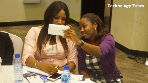 Two people seen taking selfie photograph at a mobile phone launch event in Lagos